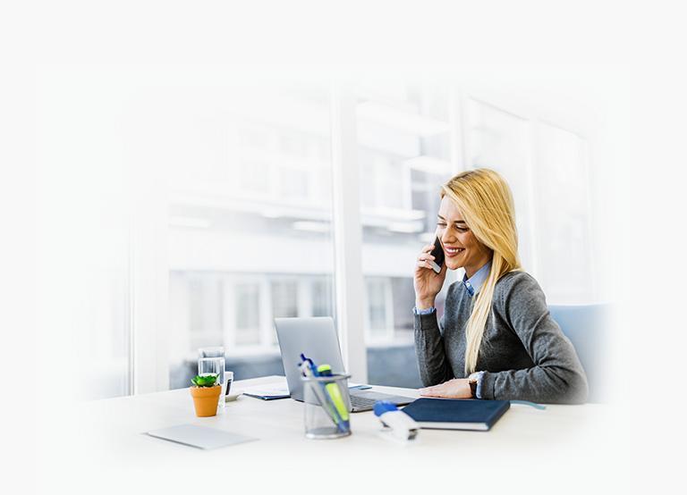Kobieta przy biurku rozmawia przez telefon